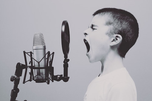 boy singing on microphone with pop filter.